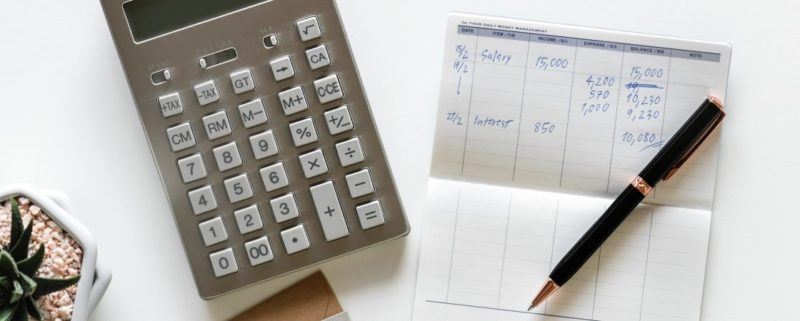 Filing your cryptocurrency tax in on paper with a calculator and pen