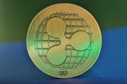 Ripple XRP logo on bronze physical coin with blue background