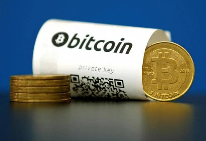 Bitcoin coins next to bitcoin paper wallet with blue background
