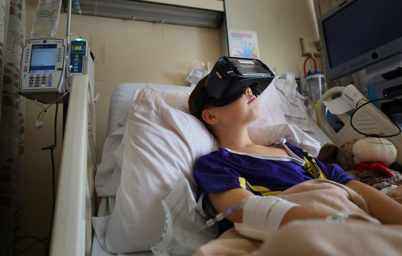 Young woman in hospital bed using VR