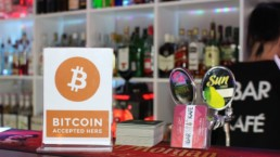 Bitcoin accepted here sign in shop with goods in the background