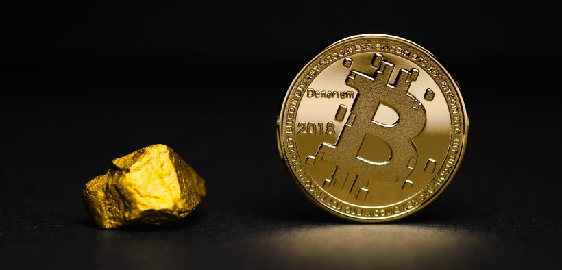 gold nugget sitting next to bitcoin coin with black back ground